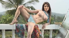 Skinny brunette with massive tits poses for the camera outdoors