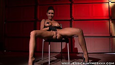 Sexy babe in fishnets and latex sits in her chair and fingers her twat